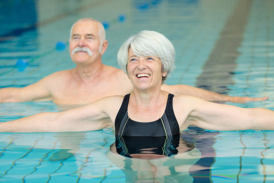 happy senior couple exercising in swimming pool
