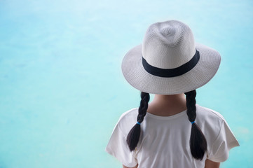 324867db back of pigtails hair girl kid with summer hat with blue sea water  background