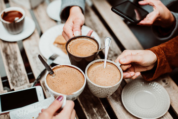 .Group of young friends drinking coffee with cakes in an outdoor cafe in Porto, Portugal. Holding their cups together. Close up. Lifestyle..