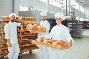 Photo sur Aluminium Boulangerie Bakers hold a tray with fresh bread in the bakery.