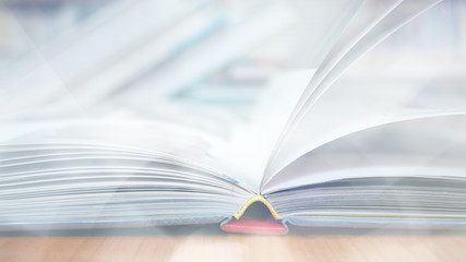 Blurred image, open book page on wood desk in the library room for business and  education background, back to school concept