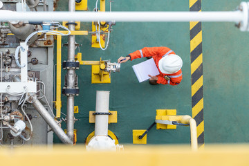 Oil and gas industry activity, operator check and inspect oil pump differential gauge and pressure transmitter as daily log sheet record for monitor production process.