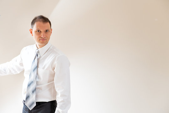 Young man businessman in business shirt tie standing by wall in room with futuristic concept light