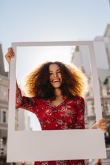Wall Mural - Beautiful woman holding a blank photo frame