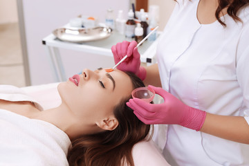 Young woman cleaning face skin in salon.