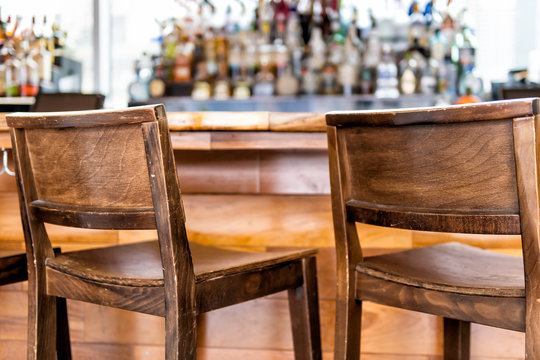 Empty wooden vintage bar stools counter row in drink establishment pub during day closeup of retro wood and nobody