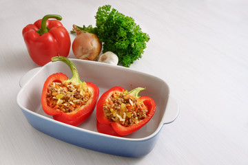 stuffed red bell pepper in a blue baking casserole and ingredients on a white table, copy space