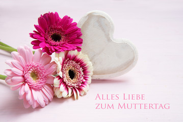 pink flowers and a white painted wooden heart on a pastel colored background,  german text Alles Liebe zum Muttertag, meaning All Love for Mother's Day