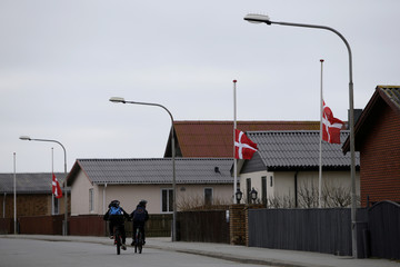 Children ride past a row of Danish flags at half-mast, flown in respect of a resident that passed away in the village of Thyboron in Jutland, Denmark