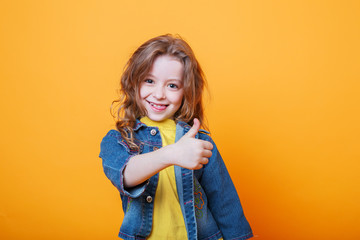 Cute little girl showing thumbs up on orange background Wall mural