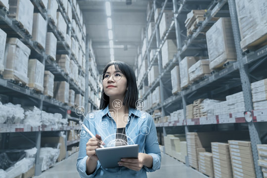 Young attractive asian manager woman looking, picking, replemishment, receiving inventory at store warehouse in warehouse management system concept. Smart ERP with iot for inventory management.