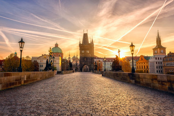 Acrylic Prints Prague Charles bridge (Karluv most) at sunrise, scenic view of the Old town with yellow sun, colorful sky and historic medieval architecture, Prague, Czech Republic