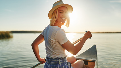 Smiling woman paddling her canoe on a lake in summer Wall mural