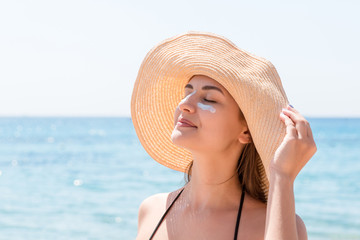 Beautiful young woman in hat is applying sunblock under her eyes and on her nose like Indian. Sun protection concept Wall mural