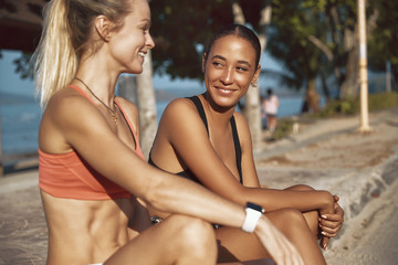 Wall Mural - Smiling young female friends sitting outdoors before a run toget