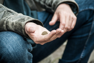 closeup of euros coins in hand of poor man sitting in the street