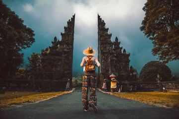Tuinposter Bali Tourist woman with backpack at vacation walking through the Hindu temple in Bali in Indonesia