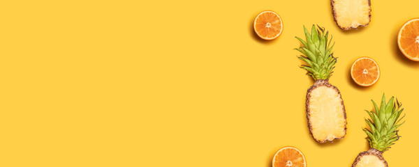 Pineapples, oranges, lemons, coconuts on yellow background. Summer fruits. Flat lay, top view, copy space Wall mural