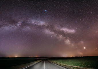 Magenta Night Starry Sky Above Country Asphalt Road In Countryside And Green Field. Night View Of Natural Glowing Stars And Milky Way Galaxy. Panorama Panoramic View