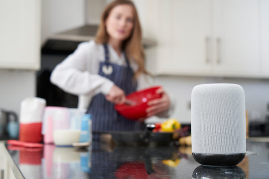 Woman Preparing Meal At Home Asking Digital Assistant Question