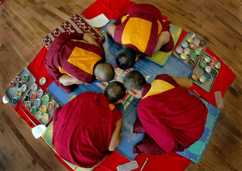 TIBETAN MONKS BEGIN CREATING A SAND MANDALA IN SURREY ART GALLERY.