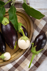 Fresh black and white eggplants on plate