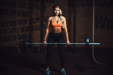 fashionable fitness woman doing heavy barbell deadlift exercise in gym. athletic beautiful white girl in cap, red top and black in sport club. Perfect fitness female figure