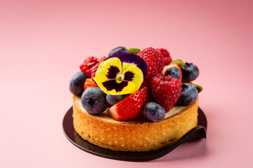 Mini tart with fresh berries on pink