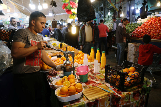 A vendor sells an orange juice for customers during the holy month of Ramadan at a market area in Amman