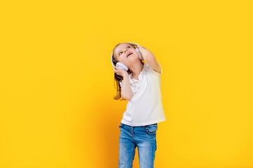 Girl of 7 years old listening to music in white wireless headphones on yellow studio background . Dancing girl. Happy small girl dancing to music. Cute child enjoying happy dance music.