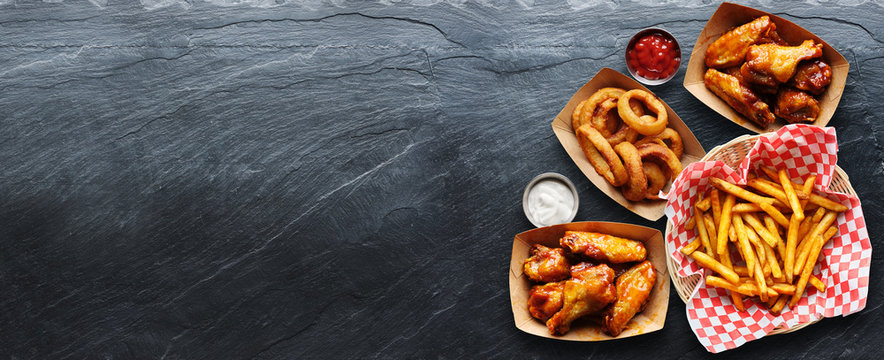 pub appetizers such as chicken wings, onion rings and french fries in panoramic composition