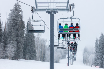 Keuken foto achterwand Gondolas Skiers ascend the chairlift to the top of the ski slopes of Steamboat Springs, in the Rocky Mountains of Colorado, lined by Pine and Aspen trees.