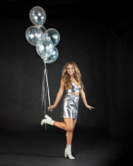 Happy young woman dancing with silver party balloons.