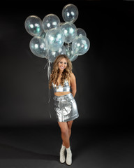 Pretty young woman in playful pose with silver party balloons.
