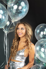 Happy young woman with silver party balloons.