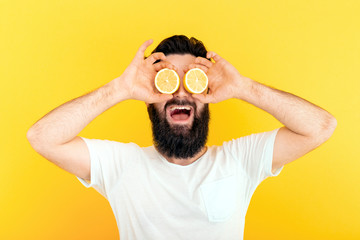 bearded hipster man holding lemon slices in front of eyes, over yellow background.