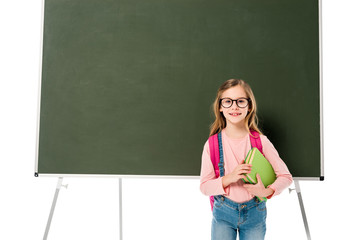front view of schoolgirl with backpack and books standing near blackboard isolated on white