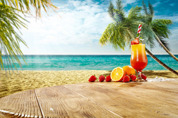 Cold summer drink on wooden table. Free space for your decoration. Beach landscape with ocean and palms. Summer sunny day.