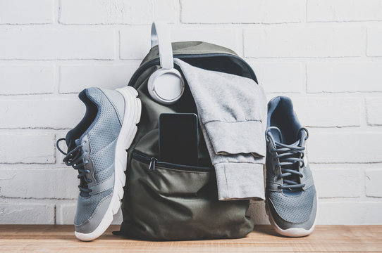 Green backpack with sportswear and sneakers. The concept of fitness or running
