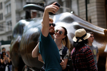 A man and woman take a selfie photograph with a smartphone in lower Manhattan in New York