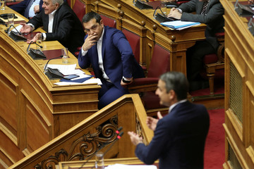 Greek Prime Minister Alexis Tsipras looks on as New Democracy party leader Kyriakos Mitsotakis addresses lawmakers during a parliamentary session on confidence vote in Athens