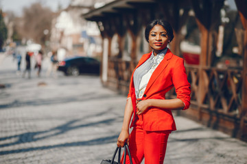 Elegant black woman standing in a summer city. Businesswoman in a red jacket