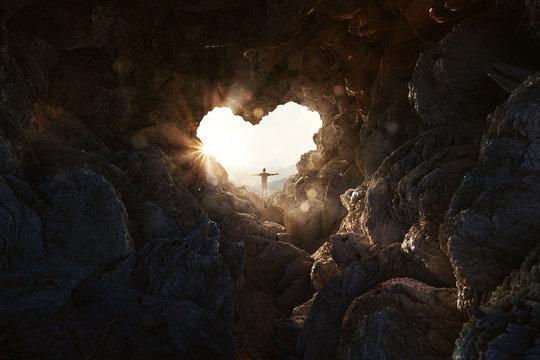 Mann steht an herzförmiger Öffnung einer Höhle und breitet Arme aus