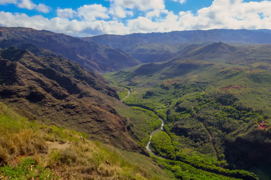 River running through green valley and mountain landscape at Waimea Canyon State Park, Kauai, Hawaii, USA