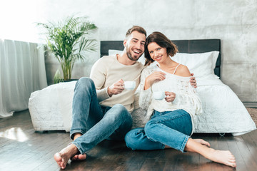handsome man hugging beautiful woman and sitting on floor with cup