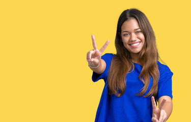 Young beautiful brunette woman wearing blue t-shirt over isolated background smiling looking to the camera showing fingers doing victory sign. Number two.