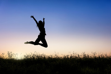 Happy woman jumping and enjoying life at sunset