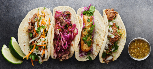 Wall Mural - four mexican street tacos with fish barbacoa and carnitas shot in panoramic composition