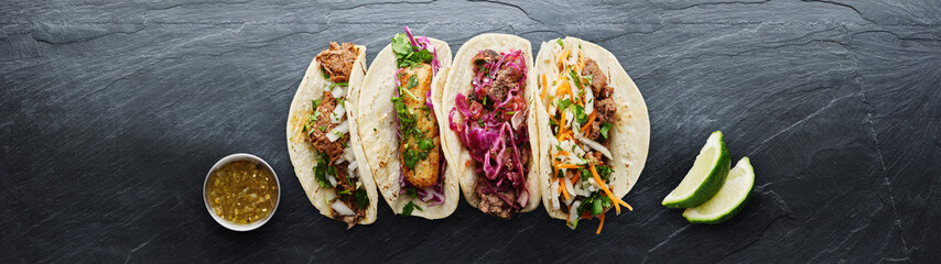 Sticker - four mexican street tacos with fish barbacoa and carnitas shot in panoramic composition