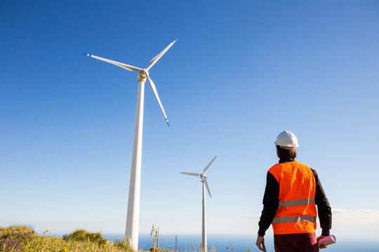 Ingegnere elettrico controlla l'impianto eolico con il gilet ad alta visibilità e casco bianco. Progetto in mano. Concetto di manutenzione
